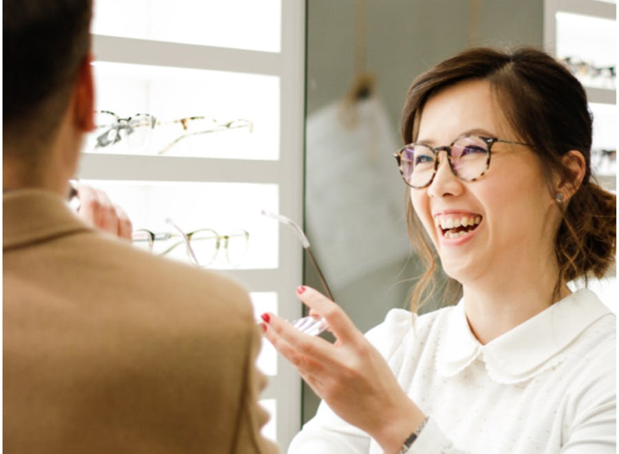 optometrist helping customer select glasses