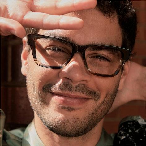 man blocking sun and smiling wearing Hugo glasses