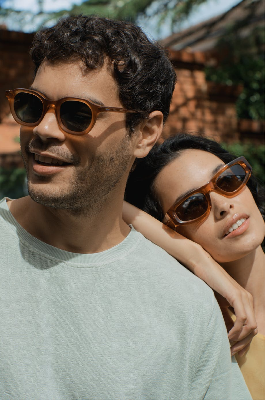 woman leaning on man both wearing sunglasses