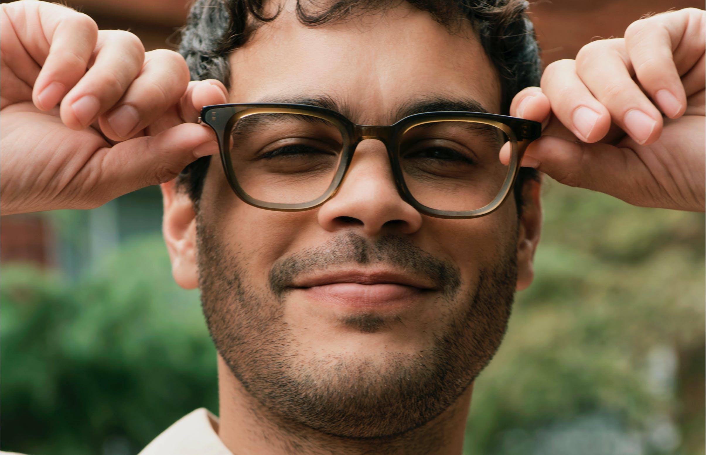 Man adjusting Nolan glasses and smiling