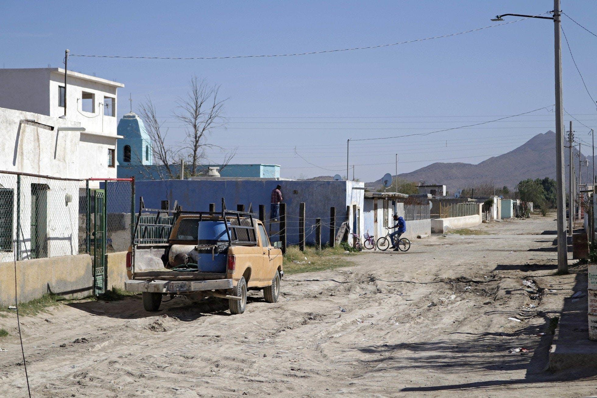 Una camioneta viaja abandonada en una de las calles sin pavimentar de Paredon. Al fondo se ve un monte.