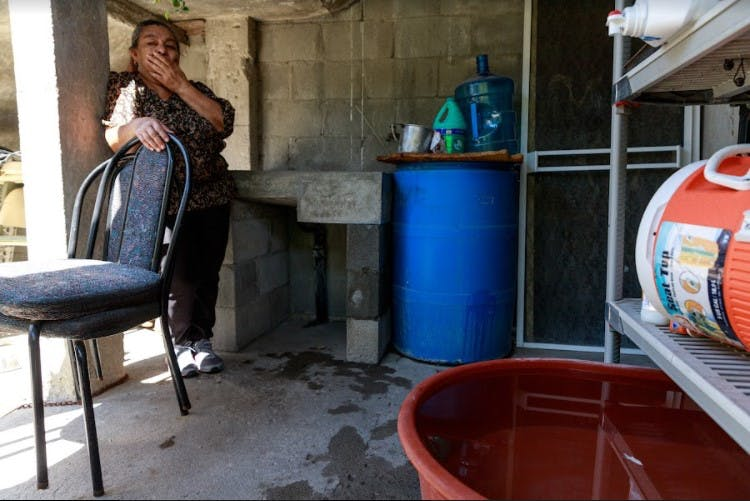 Alejandra utiliza botes de plástico para colectar agua.