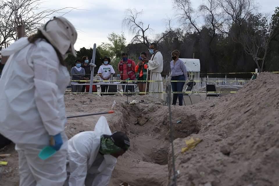 Expertos forenses realizan una exhumación, mientras las familias rezan con un cura en la parte del fondo de la imagen. Desaparecidos, Coahuila.