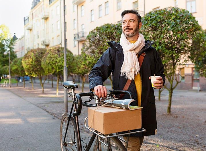 Mann schiebt ein Fahrrad, darauf liegt ein Karton aus Wellpappe
