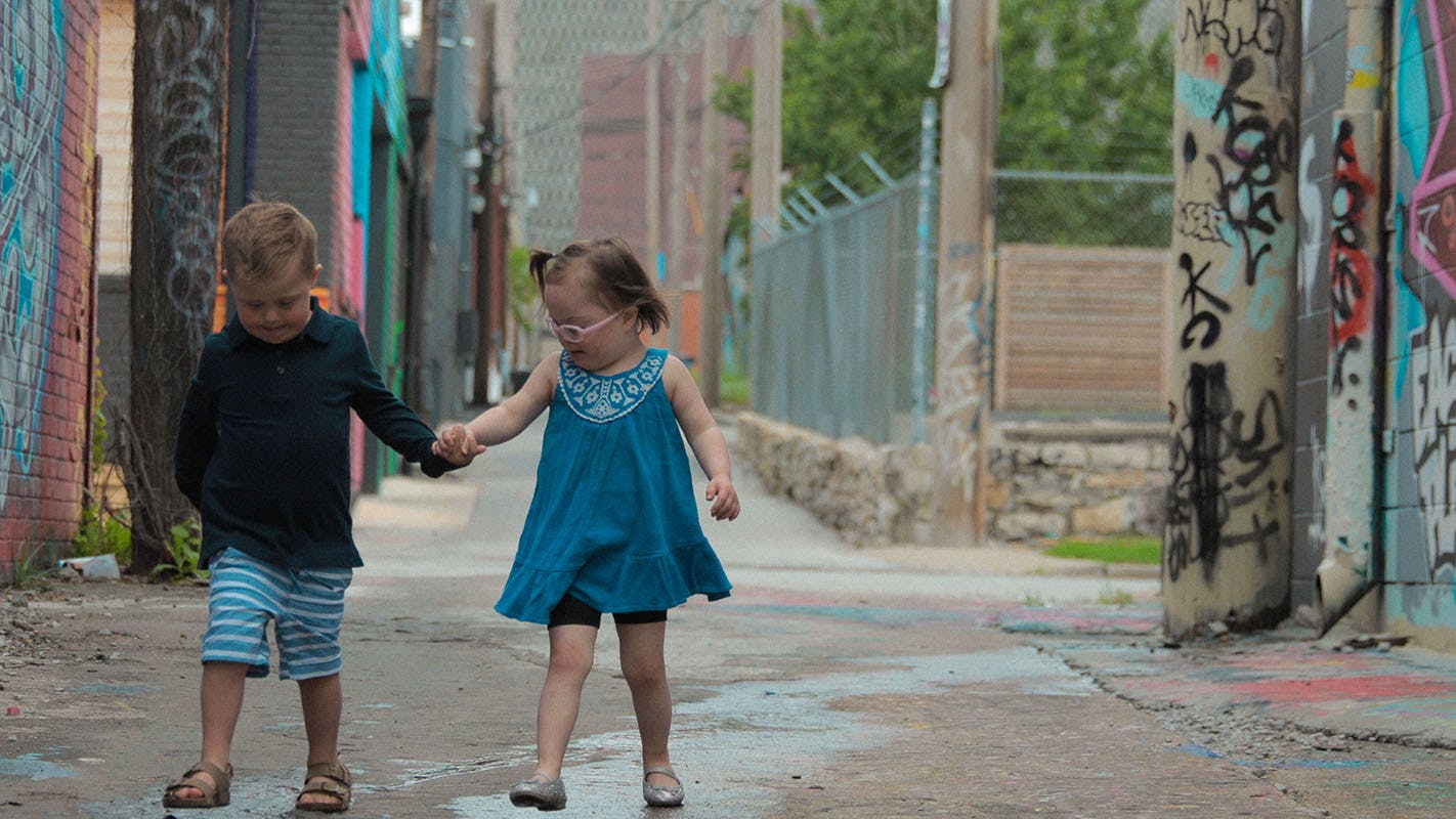 Two kids holding hands, walking in a colorful alley