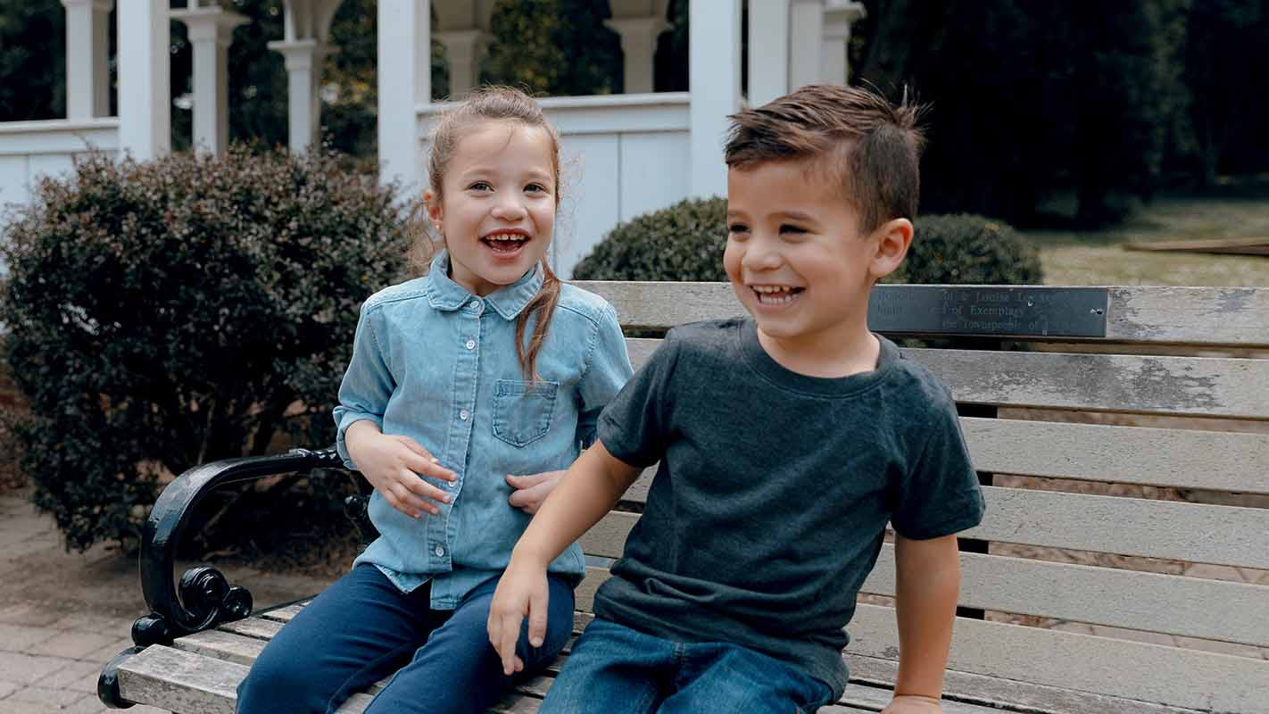 Two children laughing and smiling on a bench outside