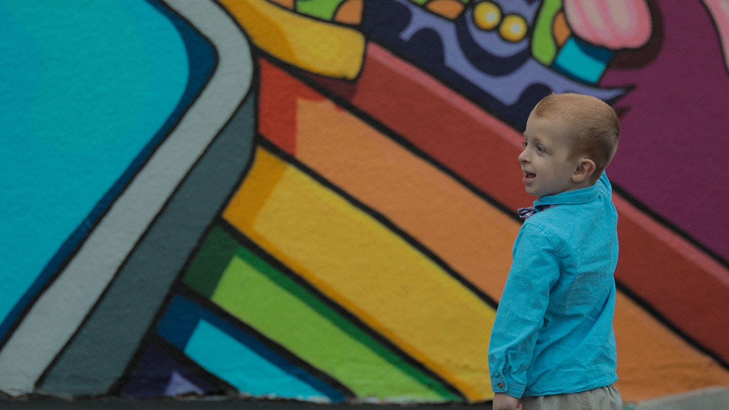 A smiling child amongst a colorful mural