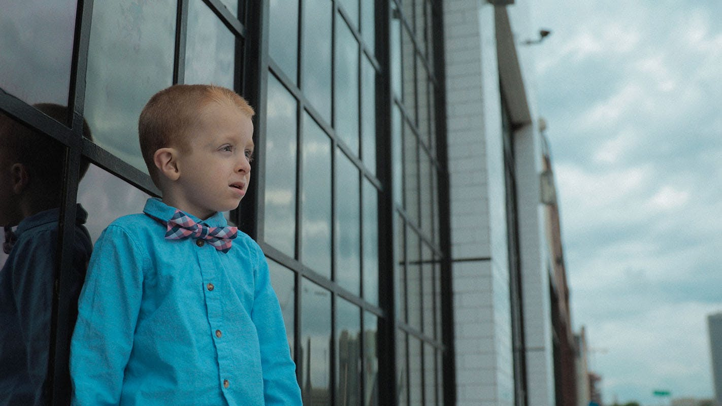 A young boy outside in front of windows, looking out into the distance