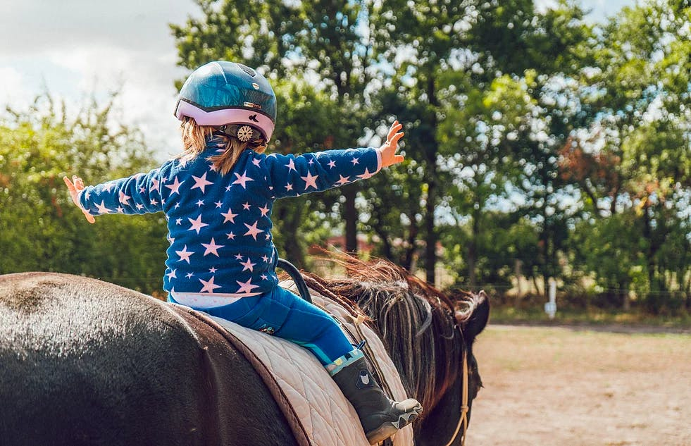 Girl riding a horse with her arms extended