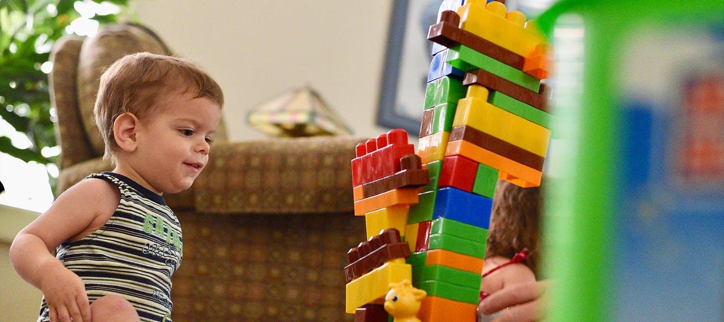 Boy building a tower of big Lego blocks