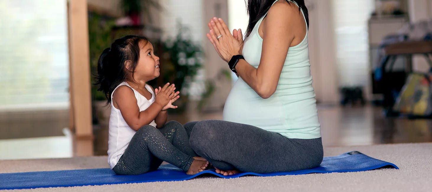 Girl and pregnant mother sitting facing each other on a yoga mat