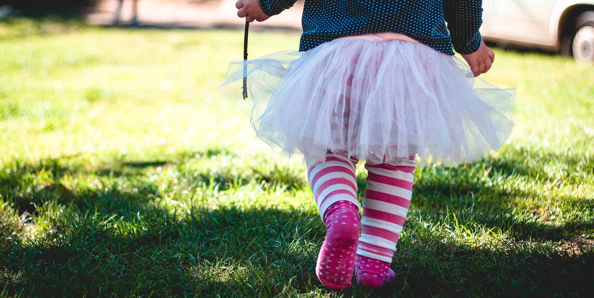 Girl with tutu walking in grass