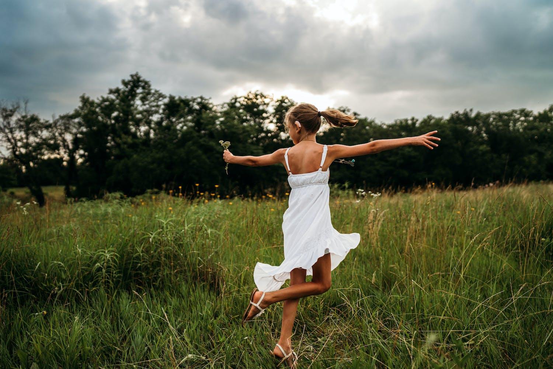 little girl dancing in field