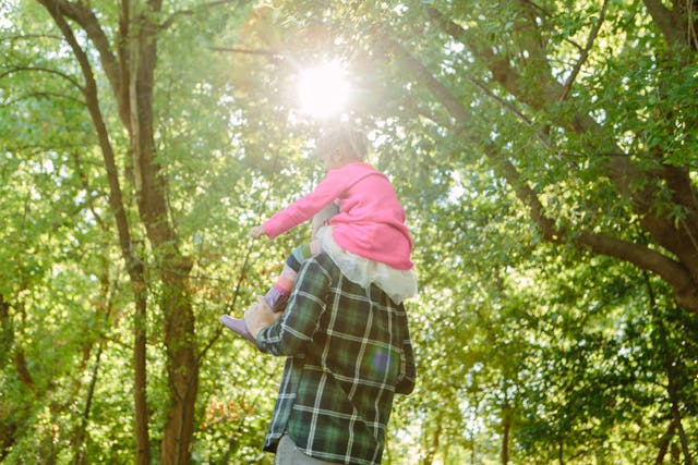 man with little girl on his shoulders in the woods