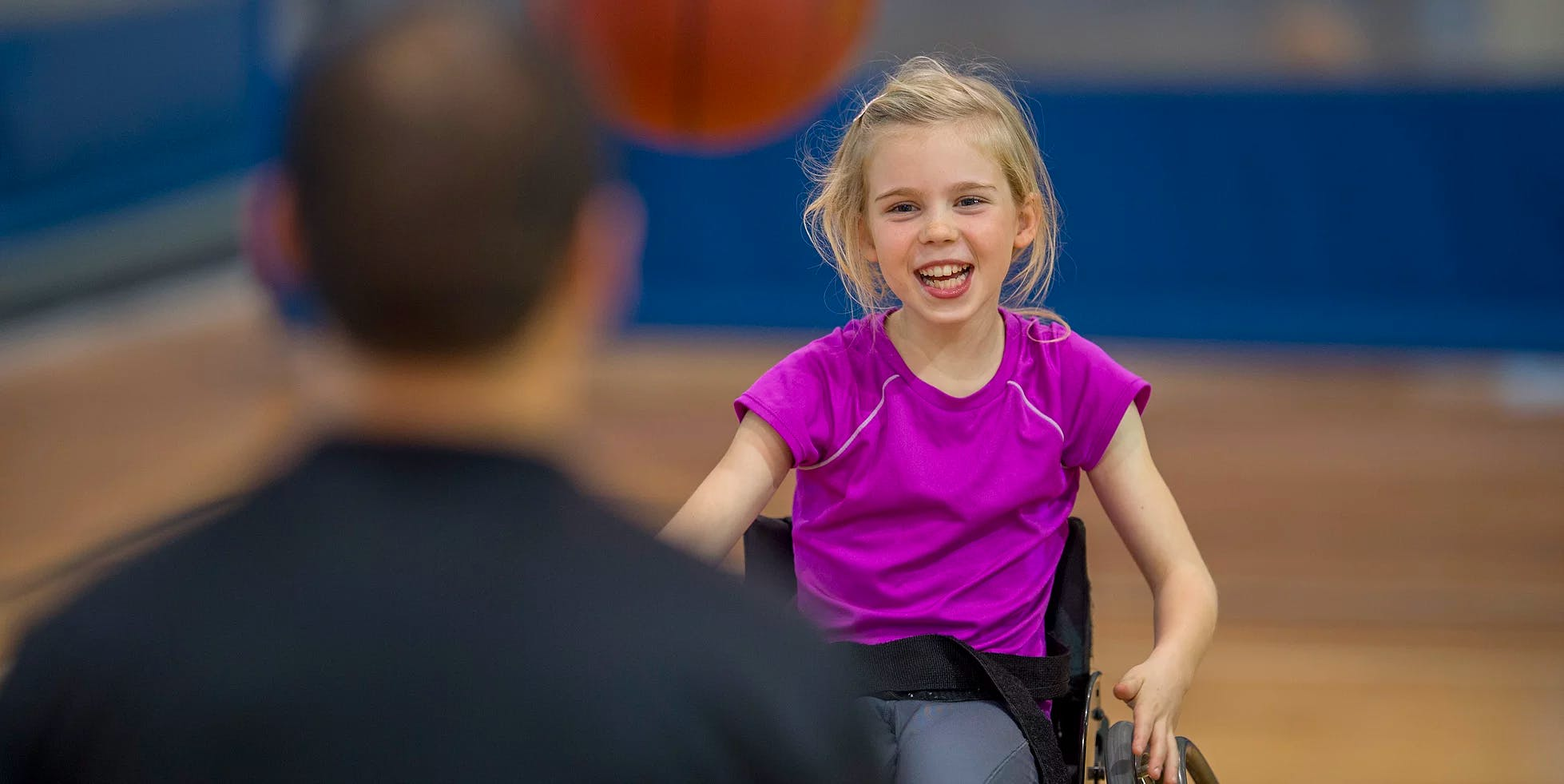 Girl with paraplegia in a wheelchair playing basketball