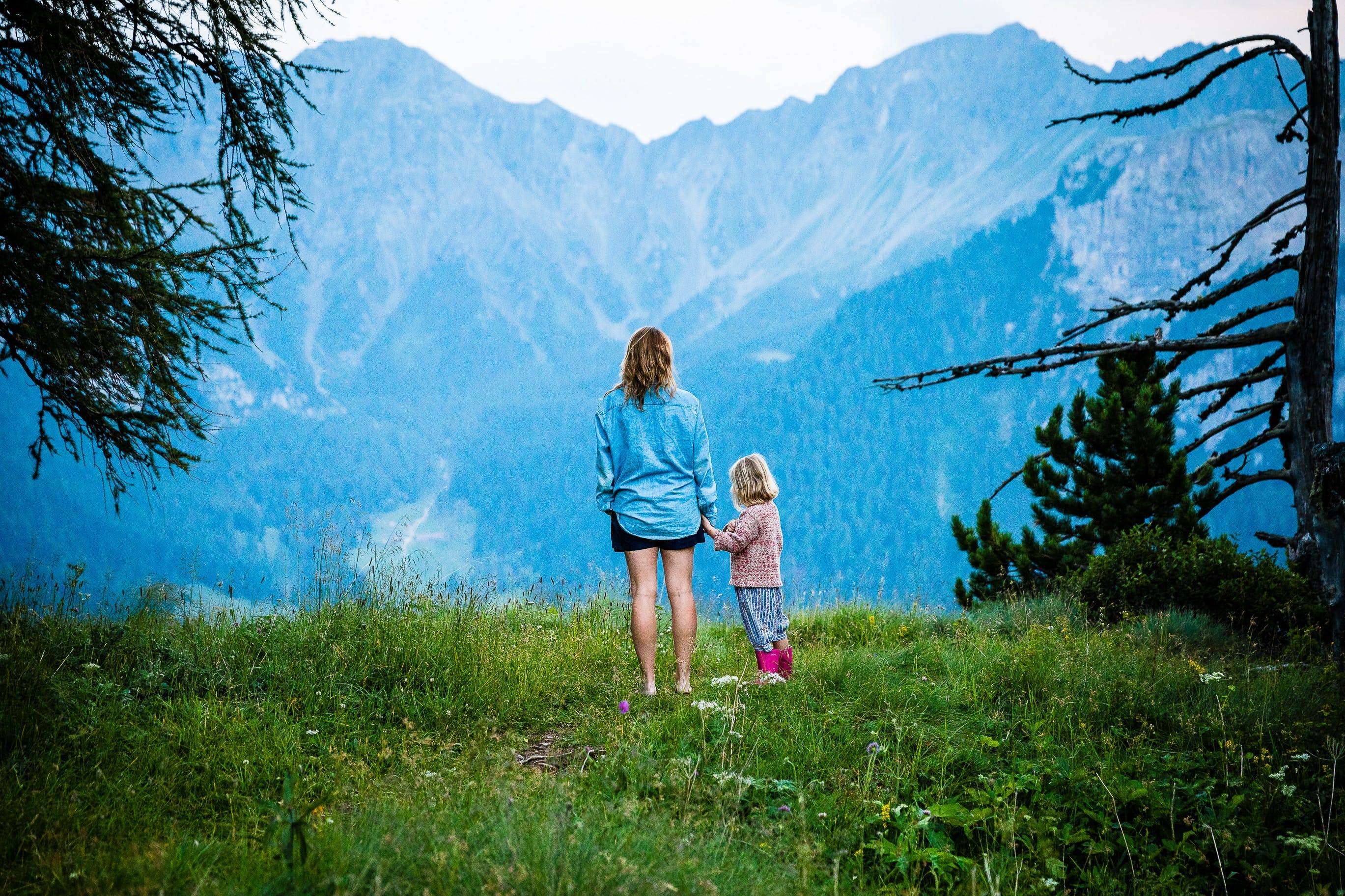 mom and girl in front of mountain