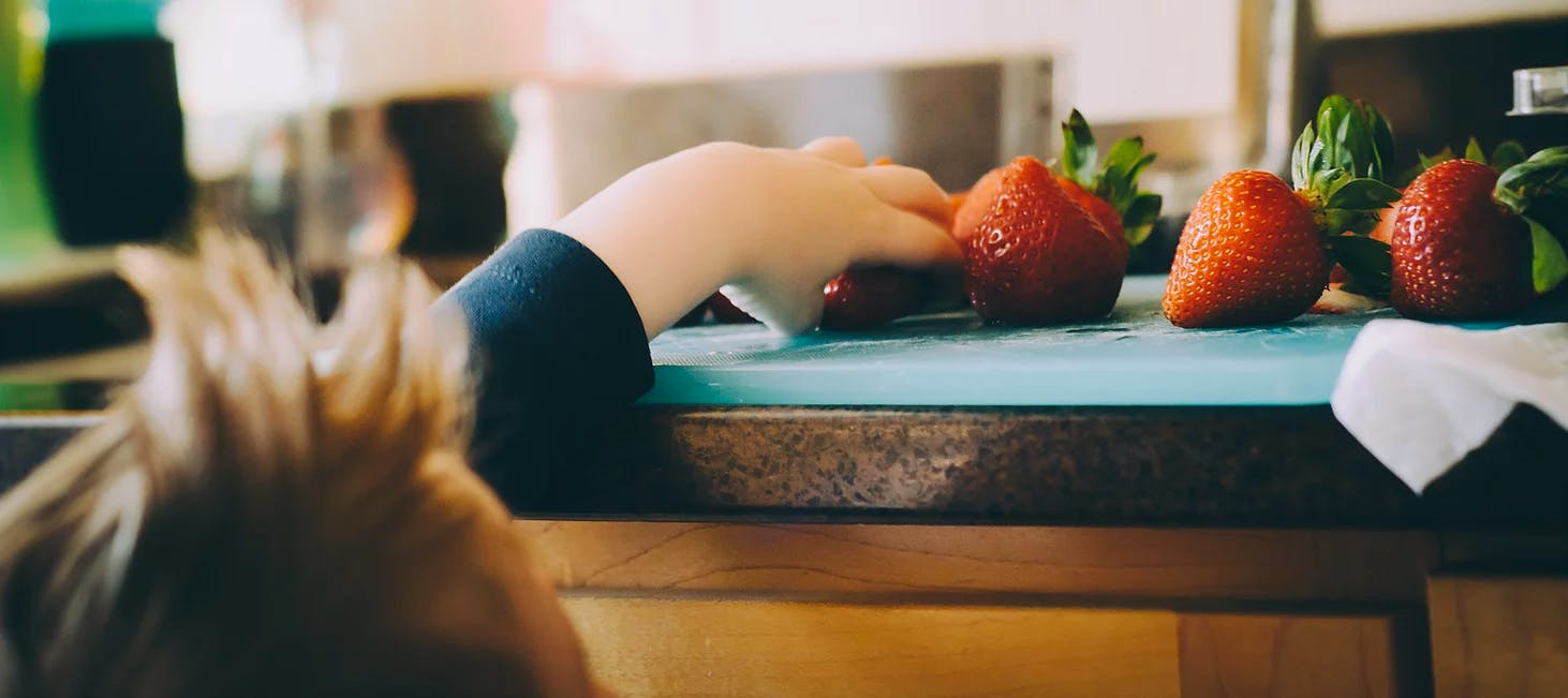 Boy reaching up to the counter to get strawberries