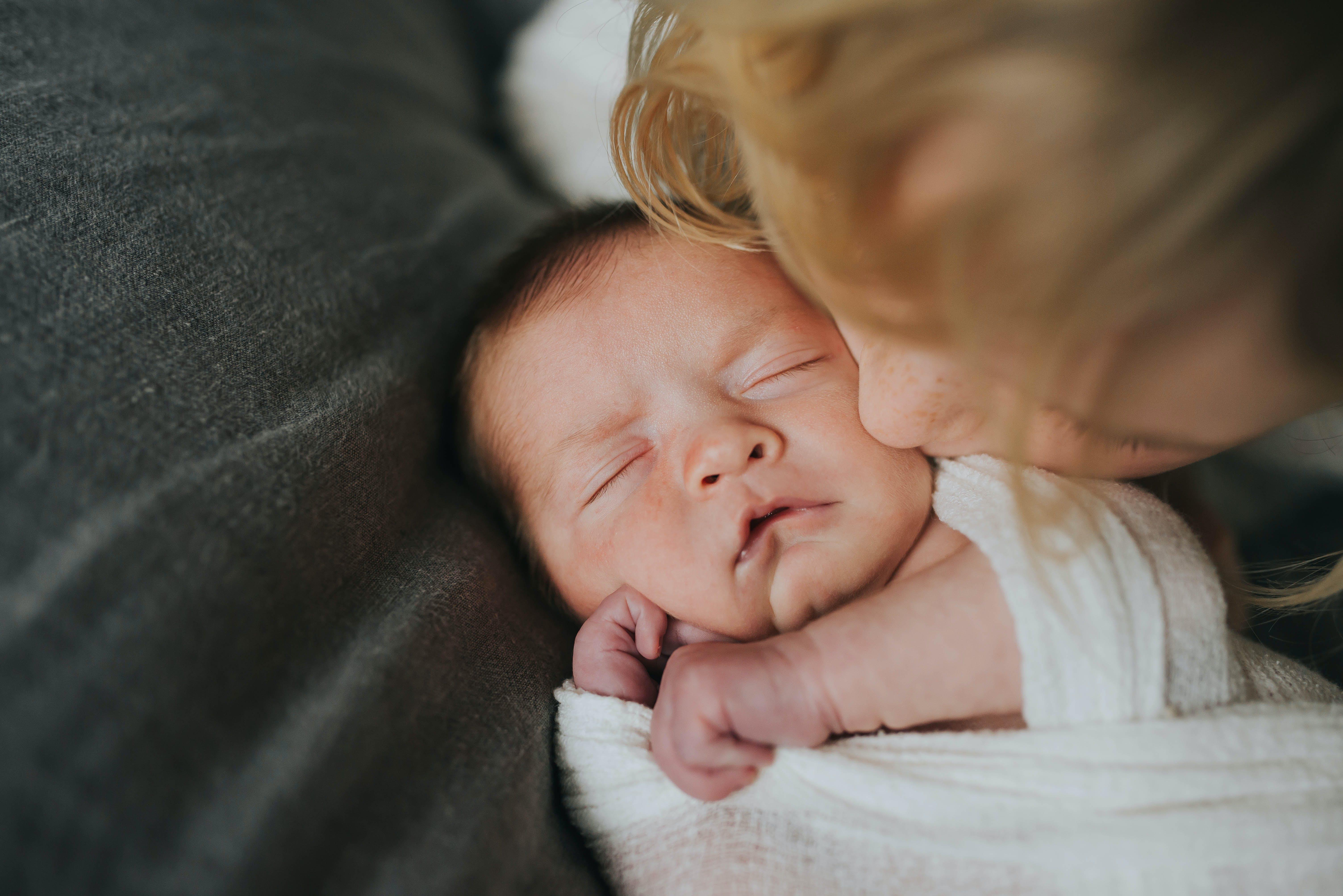 little girl kissing newborn baby