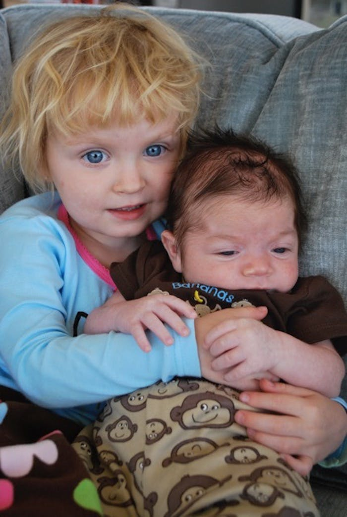 Baby Carter being hugged by his big sister