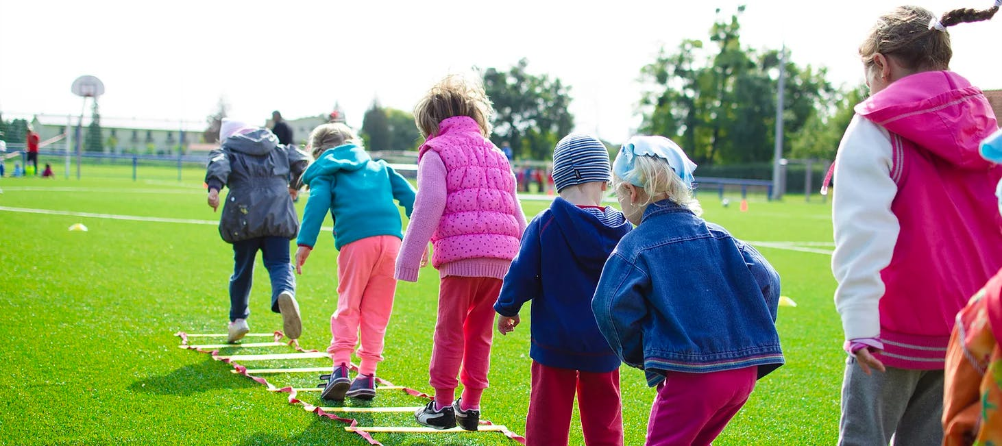 Kids in a field doing an activity in a line