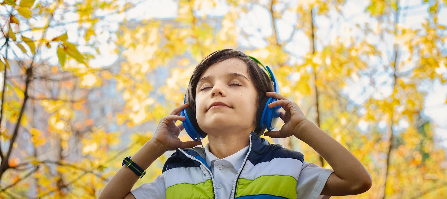Boy outdoors with headphones on and eyes closed