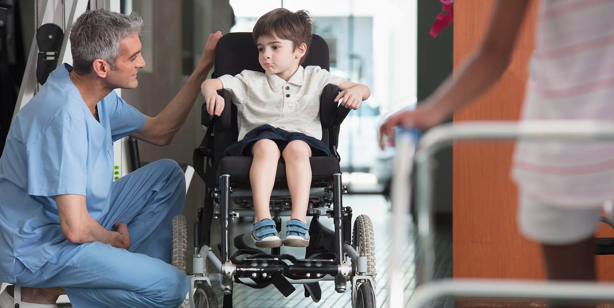 Doctor talking with boy in wheelchair