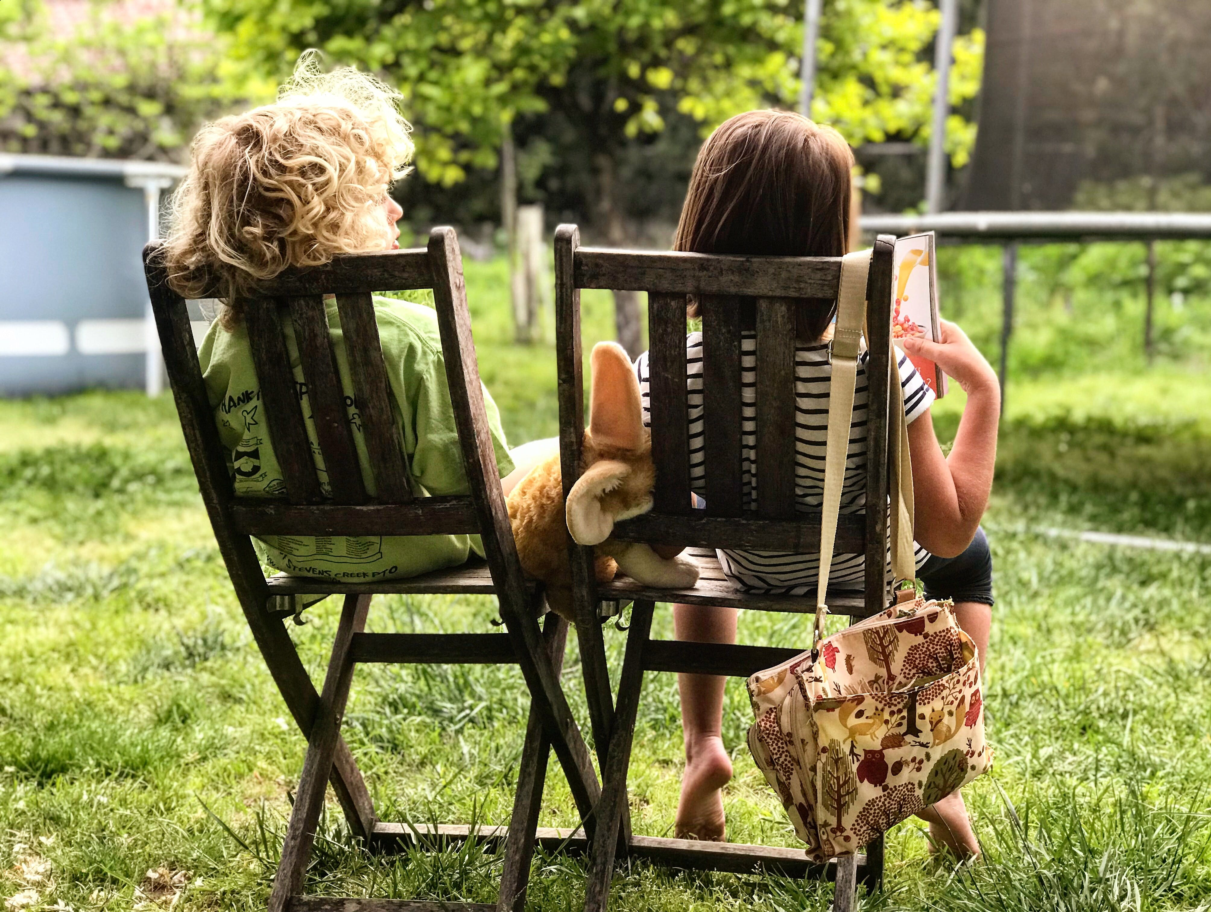 2 kids sitting in chairs outside