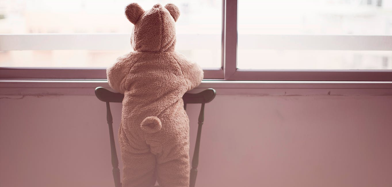 Child in bear suit looking out the window