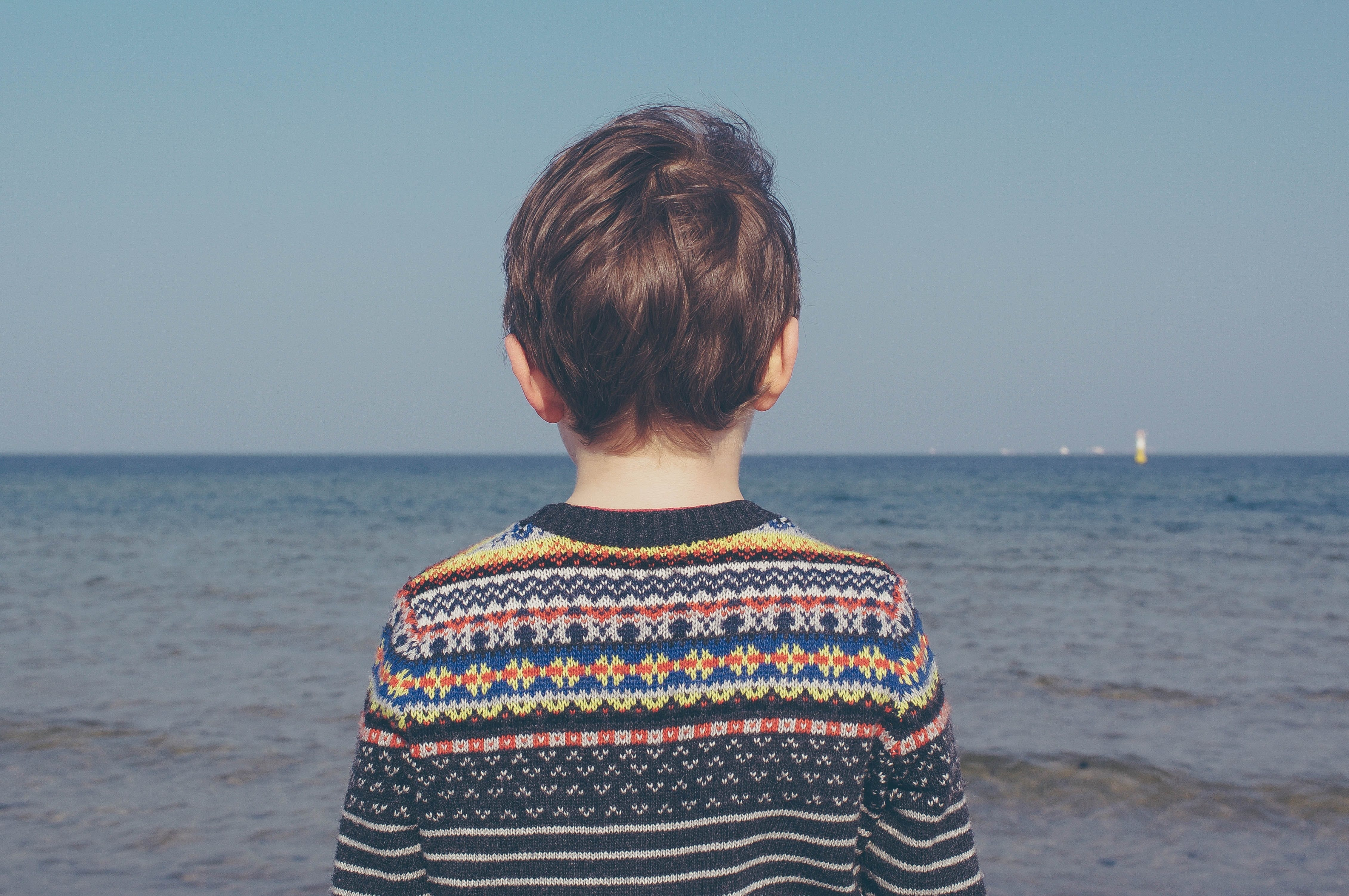 child staring at the ocean