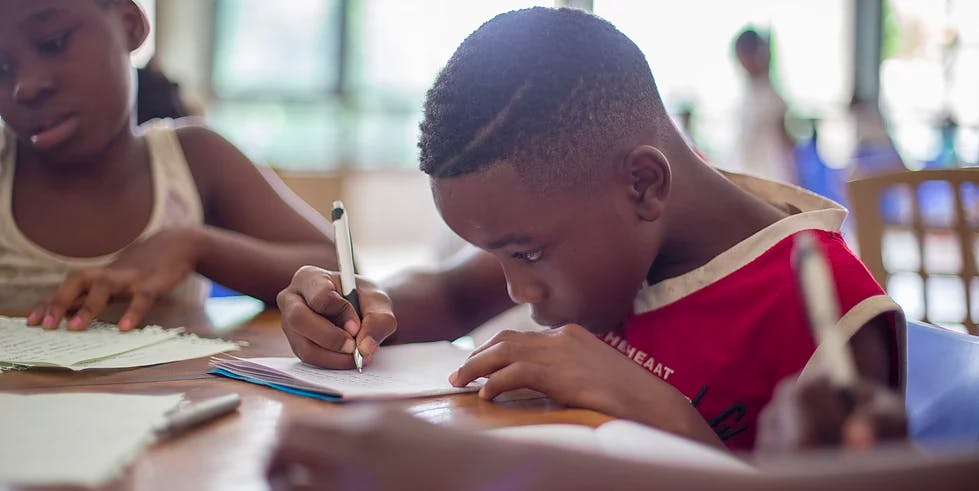 Boy with dyspraxia writing at school