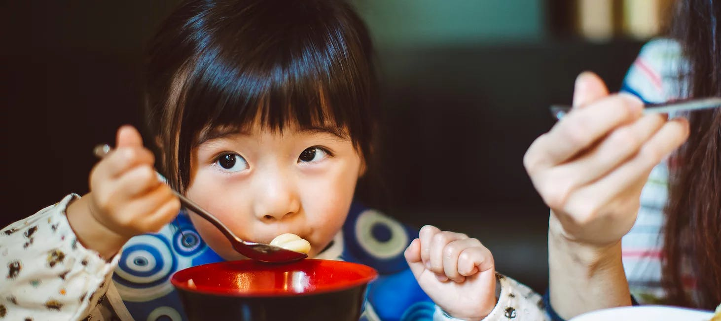 Girl eating from a bowl with a spoon
