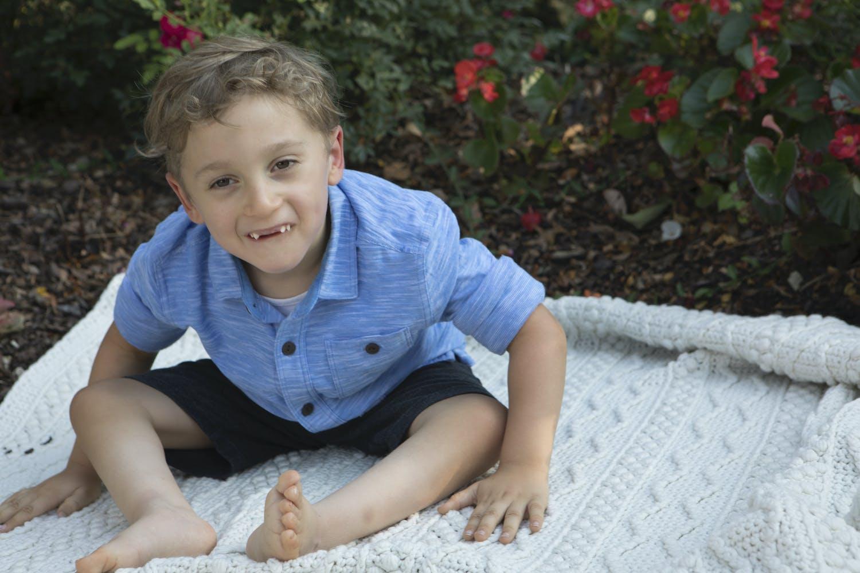 boy sitting on blanket
