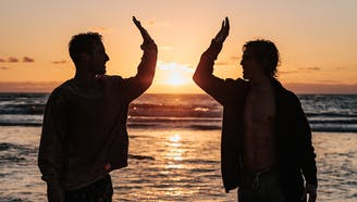 two men high-fiving on a beach during sunset