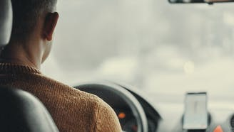 middle aged man in a brown sweater driving a car using gps