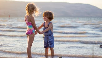 brother and sister at the beach holding hands