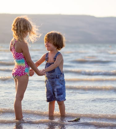 brother and sister holding hands at a beach