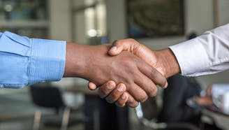 two business professionals shaking hands over deal