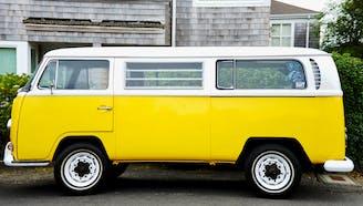 yellow volkswagen van in front of house