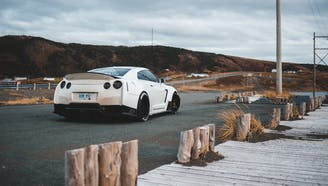 white nissan gtr parked on a cloudy day