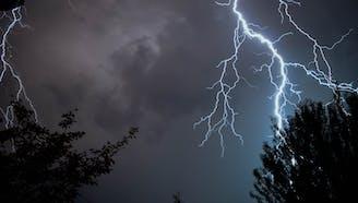 lightning across a dark, cloudy sky with trees