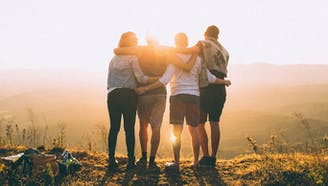four friends holding each other's backs while looking into the sunset hiking