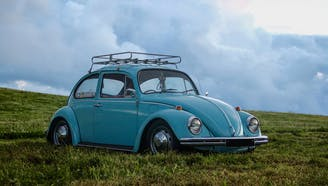 light blue volkswagen in the middle of grass with clouds