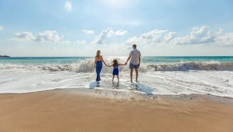 family holding hands on the beach with waves