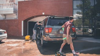 father and son washing SUV for maintenance