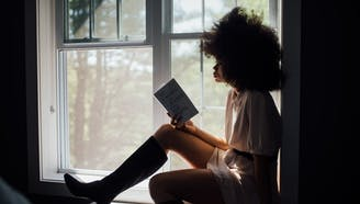 woman reading a book on the window