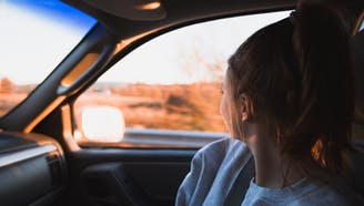 brunette young girl looking out moving car window