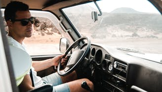 man behind the wheel of a truck driving