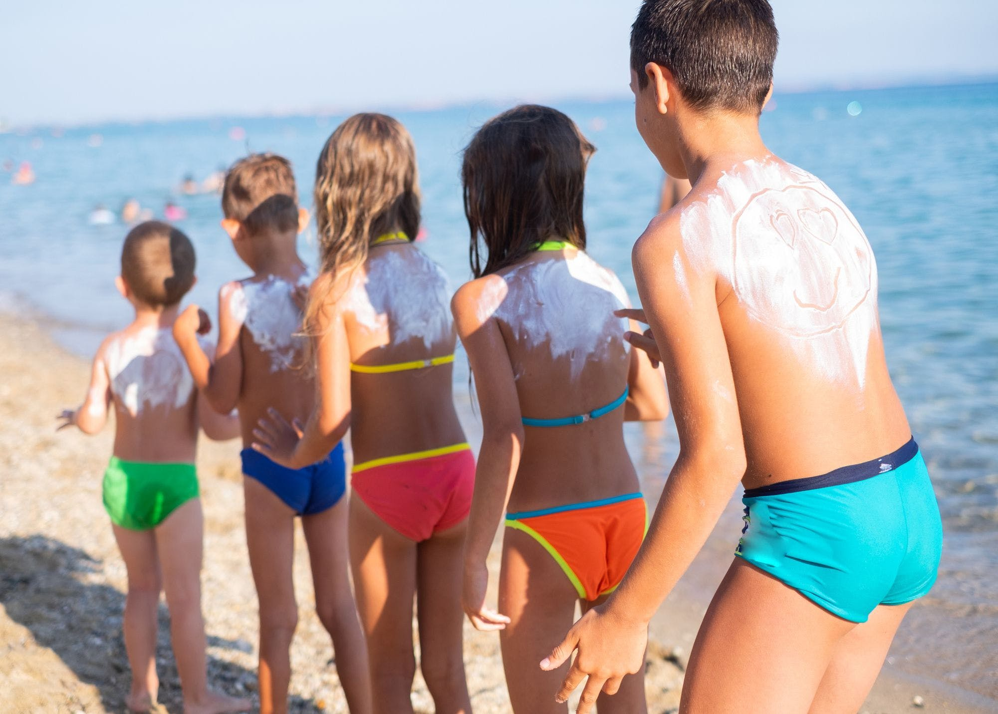 A line of five children at the beach putting sunscreen on one another.