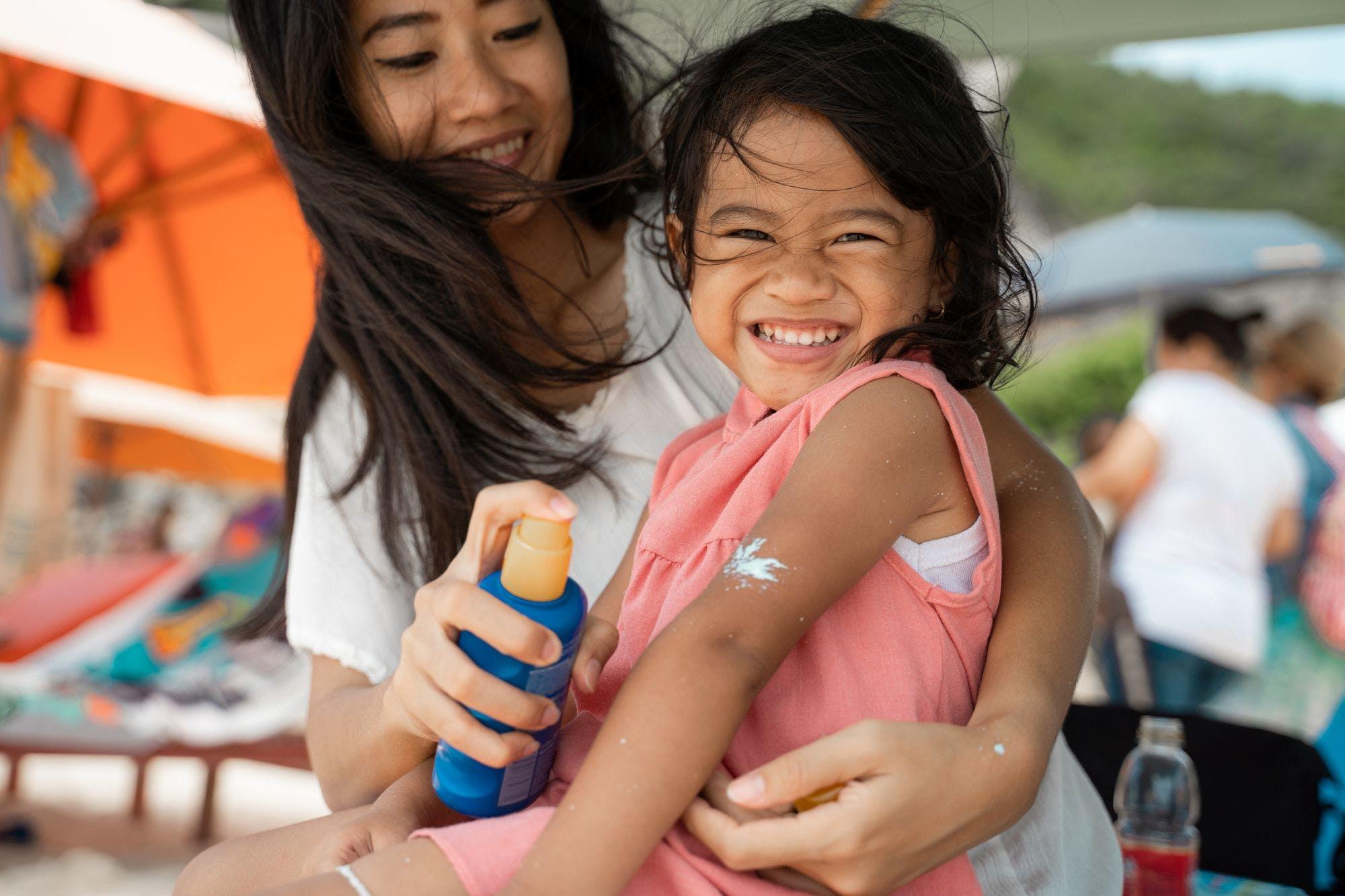 A parent sprays sunscreen onto a smiling child.