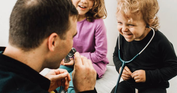 Child wearing a stethoscope laughs while doctor speaks into the other end